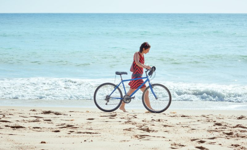 woman walking on the beach with a bicycle