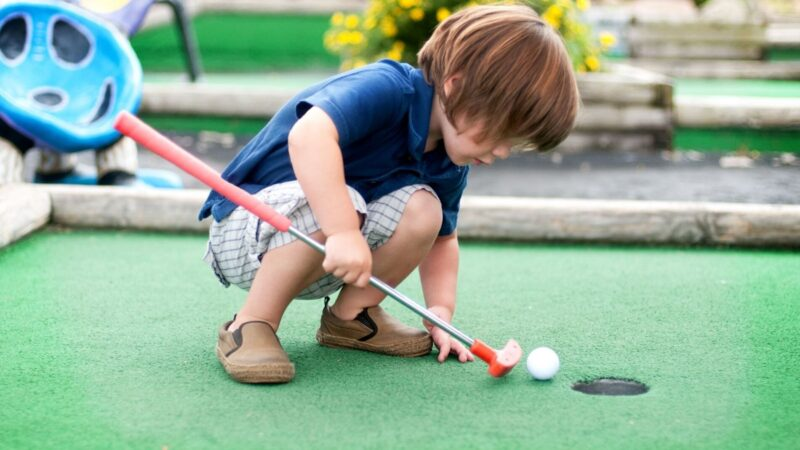 A child playing mini golf in Sarasota with the family